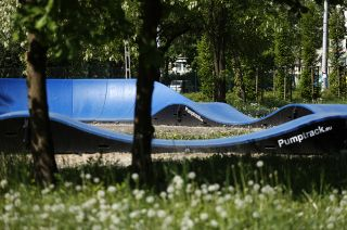 Pumptrack modulares Blau unter Frühlingsvegetation
